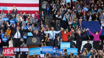 Durham, NH: (From Left to Right) Governor candidate Van Ostern, Senate candidate Maggie Hassan, Presiden Barack Obama, Senator Jeanne Shaheen, Rep. Shea Porter and Congresswoman Annie Kuster take a bow before the audience. Photo by Vaishnavee Sharma/ BU News Service.