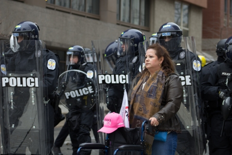 A woman silently protesters in front of a line of police at the intersection between 12th and K in D.C. on Friday, Jan. 20, 2017. Photo by Vaishnavee Sharma/BU News Service.