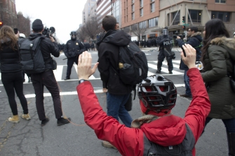 A protester sits in the street with raised hands at the Disrupt J20 protest on Friday, Jan. 20, 2017. Police block off different sections of protesters in the background. Photo by Vaishnavee Sharma/BU News Service.