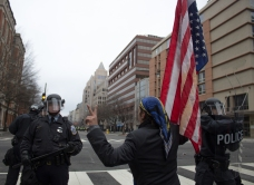 "A protester, carrying an upside down American flag, and sporting a peace sign, asks police ""is your paycheck worth this?"" Photo by Vaishnavee Sharma/BU News Service."