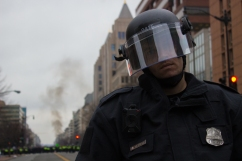A police officer looks at the camera as dark smoke looms in the background, where a different group of protesters had been blocked off by the police. Photo by Vaishnavee Sharma/BU News Service.