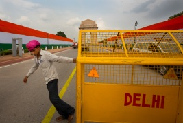 A worker barricades the road leading up to the India Gate monument, behind, as police cordon off the area for Independence Day celebrations in New Delhi, India, Monday, Aug. 14, 2017. India gained its independence from British colonial rule on August 15 in 1947. (AP Photo/Vaishnavee Sharma)