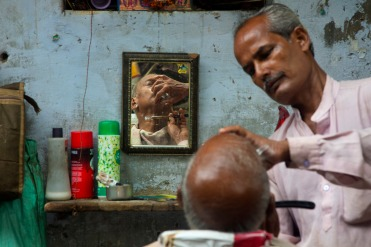 A roadside barber gives a shave in the old quarters of New Delhi, India, Tuesday, Aug. 8, 2017. Roadside barbers offer shaves, massages and hair cut options for as little as 15 rupees (US$ 0.22). (AP Photo/Vaishnavee Sharma)