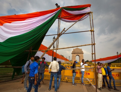 Tourists take selfies, right, as a worker erects an enclosure around the India Gate monument with a cloth with colors of the Indian flag for Independence Day celebrations in New Delhi, India, Monday, Aug. 14, 2017. India gained its independence from British colonial rule on August 15 in 1947. (AP Photo/Vaishnavee Sharma)