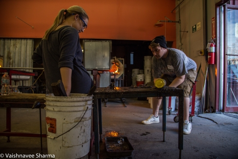 A glassblowing instructor teaches a student how to shape hot glass on November 25, 2017 at the Diablo Glass School in Roxbury, MA.