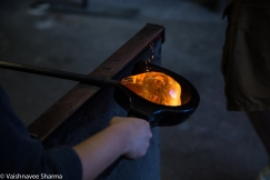 A student attempts to sculpt hot glass into a paper weight at Diablo Glass School in Roxbury, MA on November 25, 2017.