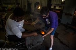 A glassblowing instructor teaches Tierra Lyons how to shape hot glass on October 30, 2017 at the Diablo Glass School in Roxbury, MA.